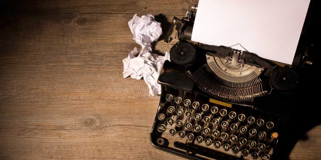 Typewriter on wooden table with screwed up paper next to it