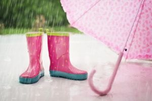 Picture of the rain and a pair of empty pink wellington boots and a pink umbrella