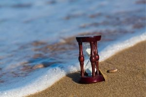 Hourglass on a beach right at the water's edge