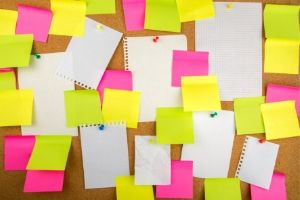 Multiple Post-Its and sheets of blank notepaper pinned to or stuck to a corkboard
