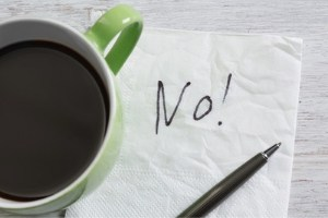 Coffee cup on top of a napkin with the word 'No!' scrawled on it.