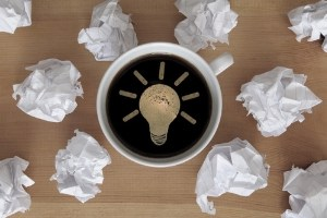Coffee cup with lightbulb icon in foam surrounded by balled up pieces of paper.